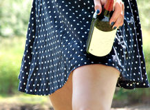 Skirt in dots with legs and bottle of wine Stock Image