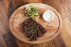 Skirt steak with salad. And sauce. Wooden background Stock Image