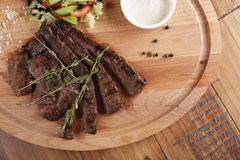 Skirt steak with salad. And sauce. Wooden background Royalty Free Stock Image