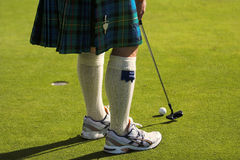 Skirted golfer. Close up golfer wearing Scottish kilt with sneekers about to putt royalty free stock images