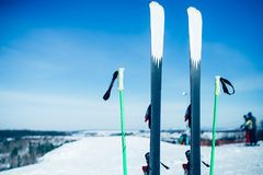 Skis and poles sticking out of the snow, nobody. Winter extreme sport concept. Mountain skiing equipment Stock Image