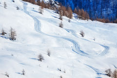 Skis or snowboarding traces on snow-covered slope Stock Photo