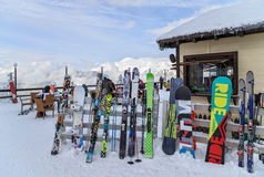 Skis and snowboards are leant against a winter cafe fence Stock Image