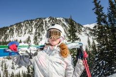 Skischutzbrillen der jungen Frau und ein Sturzhelm, der Ski in den Bergen hält Stockbild