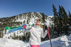 Skischutzbrillen der jungen Frau und ein Sturzhelm, der Ski in den Bergen hält Stockfoto
