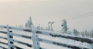 Skisessellift mit Skifahrern in Schnee-mit einer Kappe bedeckten Bergen stock footage