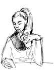 Skissa av en flicka som dricker till och med ett sugrör och ser telefonen Arkivbild