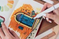 Skissa teckningen av den ljusa dörren vid markörer i sketchbook med woma royaltyfri bild