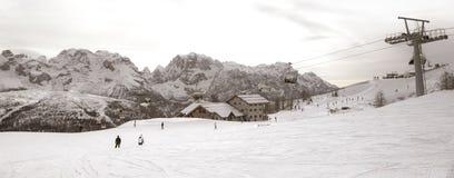 Skisteigungen mit Skifahrern bei Sonnenuntergang lizenzfreie stockbilder