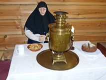 The skitnica believer at the table drinking tea from a samovar. At the inn. Museum-reserve of wooden architecture and folk art Nizhnyaya Sinyachikha, Russia royalty free stock photos
