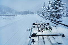 Skitour mit Skis auf dem Autodach während der Schneefälle Stockfoto
