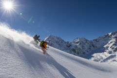 Skitouring downhill - powder skiing. Daparture in the powder snow Royalty Free Stock Photo