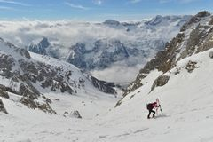 Skitouring. Woman skitouring in a breathtaking surroundings of high mountains. Italy, Julian Alps, Forca de la Val Stock Photos