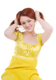 Skittish young woman's plays with her red hair. Sexual and skittish young woman in yellow dress plays with her red hair on white background Stock Image