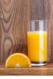 Skiva av apelsinen och ett exponeringsglas av orange fruktsaft Arkivfoto
