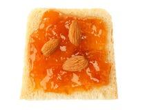Skiva av bröd med aprikosdriftstopp och mandlar som isoleras Royaltyfria Foton