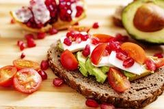 Skiva av bröd med avokadot, den körsbärsröda tomaten, granatäpplefrö och ny ost arkivbilder