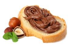 Skiva av bröd med chokladpralin med hasselnöten som isoleras på vit bakgrund Arkivbild