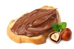 Skiva av bröd med chokladpralin med hasselnöten som isoleras på vit bakgrund Arkivfoton