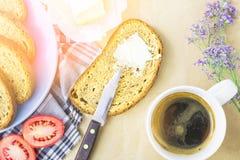Skiva av bröd med fördelande smör och en kopp kaffe för frukost på en bakgrund för kraft papper, en solig morgonbild arkivbild