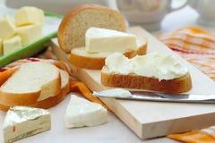 Skiva av bröd med gräddost och smör för frukost arkivfoton