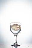 Skiva av citrondroppar i ett exponeringsglas av vatten Arkivfoto