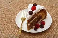 Skiva av den hemlagade ljusbruna kakan som dekoreras med piskade kr?m och hallon fotografering för bildbyråer