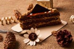 Skiva av den ljusbruna kakan med choklad Fotografering för Bildbyråer