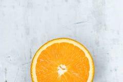 Skiva av den mogna saftiga vibrerande livliga färgapelsinen på Gray Stone Concrete Metal Background Hög upplösningsmataffisch vit arkivfoto