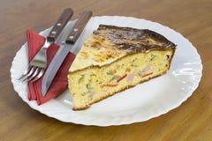 Skiva av den nytt bakade cornbreaden med grönsaker och skinka på den vita plattan Royaltyfri Fotografi
