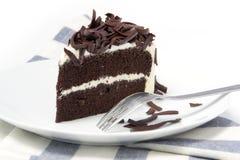 Skiva av den rika chokladkakan på plattan Royaltyfri Bild