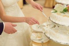 Skiva av den vita bröllopstårtan Arkivfoton