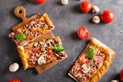 Skiva av fyrkantig pizza med basilikatomater och champinjoner på ett träbräde Royaltyfri Foto
