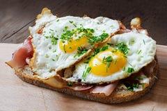 Skiva av lantligt bröd med skinka och stekte ägg Arkivfoton