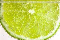 Skiva av limefrukt i vattnet med bubblor Arkivbilder