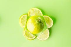 Skiva av limefrukt runt om en som är hel på grön bakgrund, horisontalskott Royaltyfri Foto