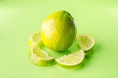 Skiva av limefrukt runt om en som är hel på grön bakgrund, horisontalskott Arkivbilder