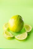 Skiva av limefrukt runt om en som är hel på grön bakgrund, lodlinjeskott Royaltyfri Fotografi