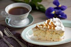 Skiva av marängkakan och en kopp te och en iris arkivfoton