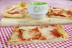 Skiva av margheritapizza med koppen av cappuccino Fotografering för Bildbyråer
