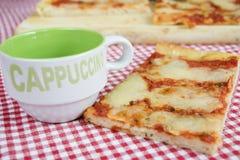 Skiva av margheritapizza med koppen av cappuccino Arkivbild