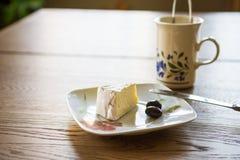 Skiva av mjuk ost och två oliv Royaltyfri Bild