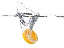 Skiva av orange frukt som faller in i vatten, med en färgstänk, vit b royaltyfria bilder