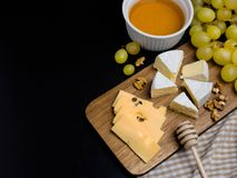 Skiva av ost, muttrar, honung och druvor på träskärbräda Camembertost och edamost med plädtyg fotografering för bildbyråer