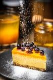 Skiva av ostkaka med bär på en blå platta Sugar Snow pudrat socker arkivfoton