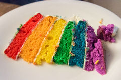 Skiva av regnbågefödelsedagkakan Royaltyfri Bild