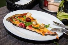 Skiva av svart pizza med ost- och bacon- och basilikatranbär Arkivfoto
