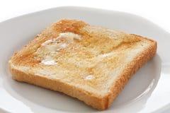 Skiva av vit bredd smör på rostat bröd Arkivbild