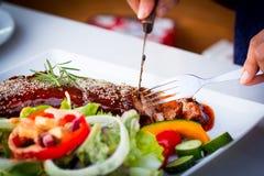 Skiva BBQ-stöd - marinerade grisköttstöd med sallad Arkivbild