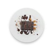 Skiva för chokladkaka med muttern på plattan som isoleras på vit Arkivbild